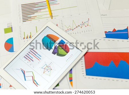 Financial charts on the table with tablet - stock photo