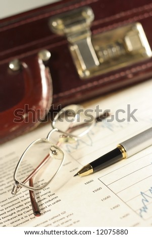 Financial charts, pen, glasses and briefcase. - stock photo