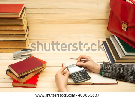 Financial concept. Businessman counting profit and losses, analyzing financial results. On a wooden table books, documents, calculator, red briefcase. Copy space. - stock photo