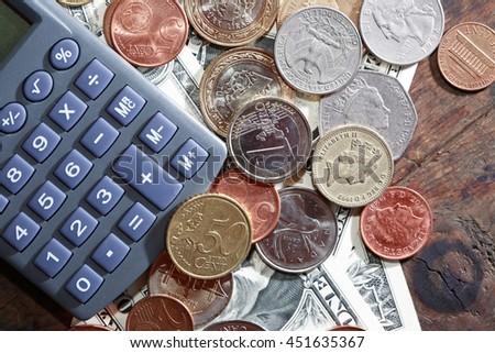 Financial concept. Calculator near various world currency closeup - stock photo