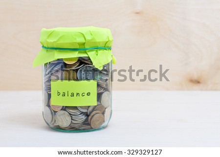 Financial concept. Coins in glass money jar with balance label. Wooden background - stock photo