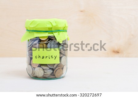 Financial concept. Coins in glass money jar with charity label. Wooden background - stock photo