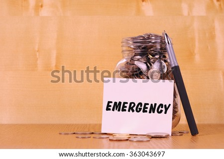 Financial concept. Coins in glass money jar with emergency label. Wooden background - stock photo