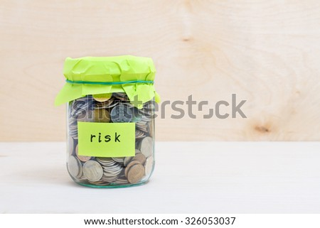 Financial concept. Coins in glass money jar with risk label. Wooden background - stock photo