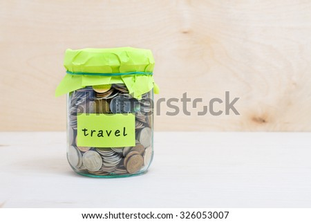 Financial concept. Coins in glass money jar with travel label. Wooden background - stock photo