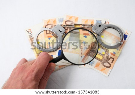 Financial Concept Loupe,Handcuffs and Money on a White Background - stock photo