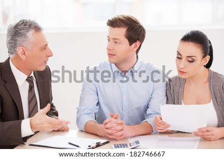 Financial consultation. Young couple sitting together at the table while senior man in formalwear telling something and gesturing  - stock photo