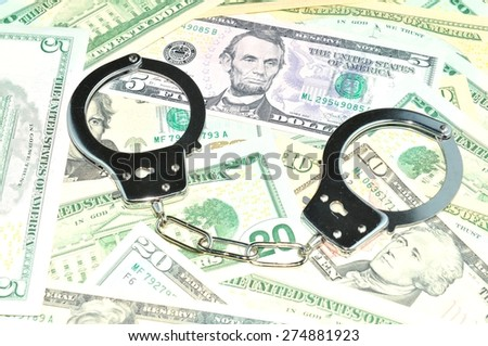 Financial crime concept with handcuffs on money background - stock photo