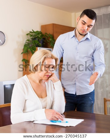 Financial crisis in family of upset adult son and his senior mature mother  - stock photo