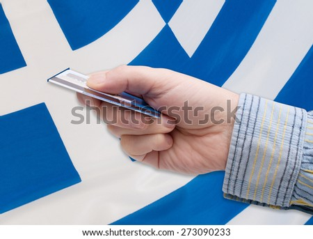 Financial Crisis in Greece - Man's Hand With Banking Card Greek flag - stock photo