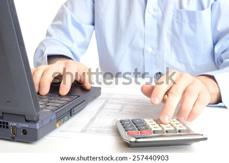 Financial data analyzing. Close-up photo of a businessman's hand writing and counting on calculator in office. Selective focus - stock photo