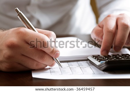 Financial data analyzing. Counting business data with calculator on the table closeup - stock photo