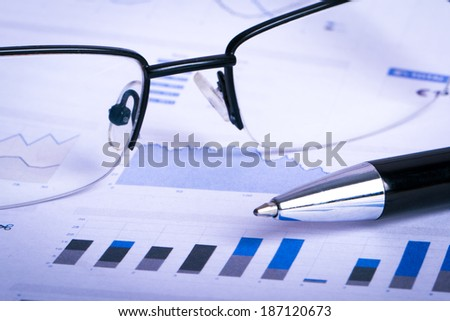 Financial data chart graphs and analysis with pen, eye glasses on business table. - stock photo