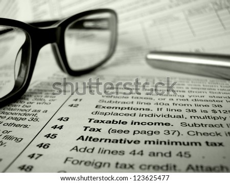 Financial Image Of Some Tax Forms With Glasses And A Pen - stock photo