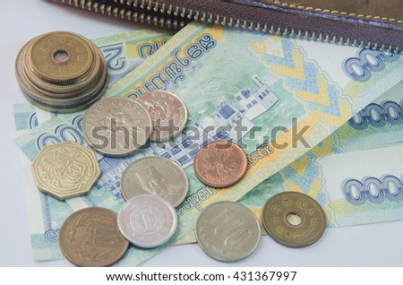 Financial investments across different currencies. Wallet insert currency of the country in both Asia and Europe. - stock photo