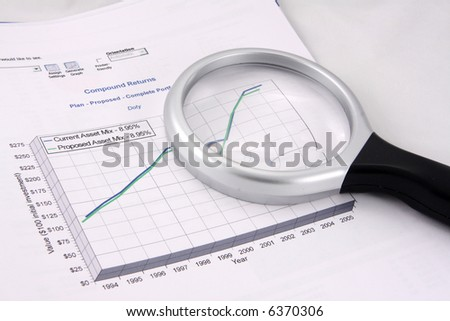 Financial investments chart showing proposed growth in assets. Magnifying glass sits on top. - stock photo