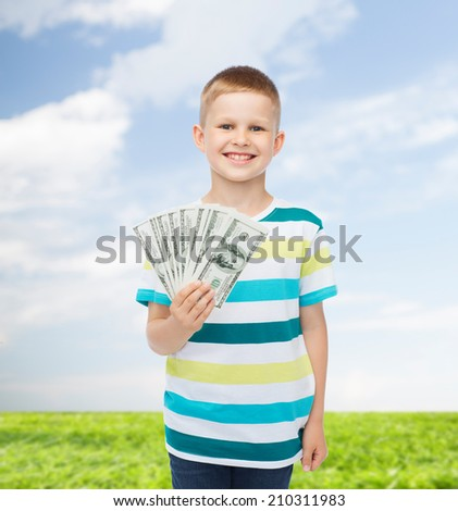 financial, planning, childhood and environment concept - smiling boy holding dollar cash money in his hand over natural background - stock photo