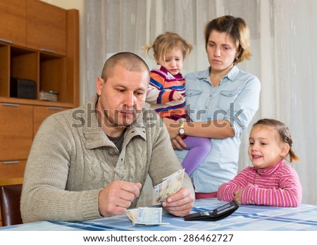Financial problems in family. Woman with children against husband at home with money - stock photo