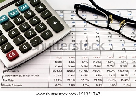Financial reports with calculator and glasses - stock photo