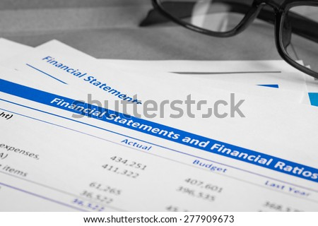 Financial statement letter on brown envelope and eyeglass, business concept; document is mock-up - stock photo