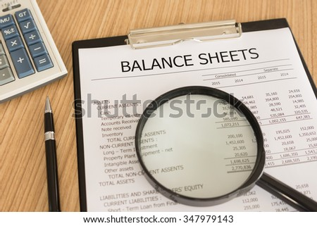 financial statement with magnifier, pen, summary report and calculator on auditor's desk. - stock photo