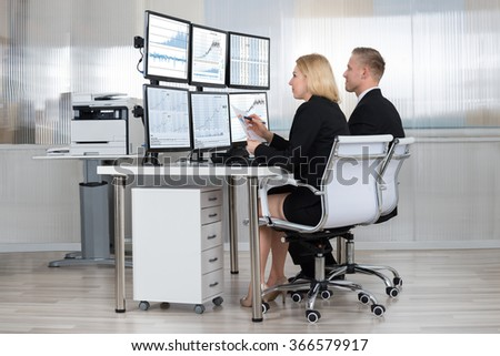 Financial workers analyzing data displayed on computer screens at desk in office - stock photo