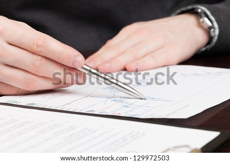 Financial world with business people and everything related to it - signing document - stock photo