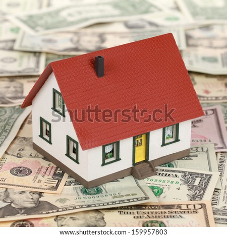 Financing a real estate with a model house on Dollar banknotes - stock photo
