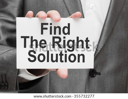 Find The Right Solution. Businessman holding a card with a message text written on it - stock photo