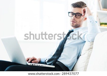 Finding a peaceful place for work. Confident young businessman working on laptop while sitting on sofa  - stock photo