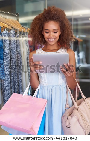Finding shopping trends online and at the mall - stock photo