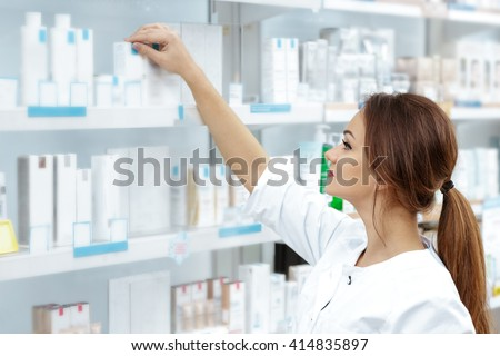 Finding what customers need. Shot of an attractive young pharmacist checking stock in an aisle. - stock photo