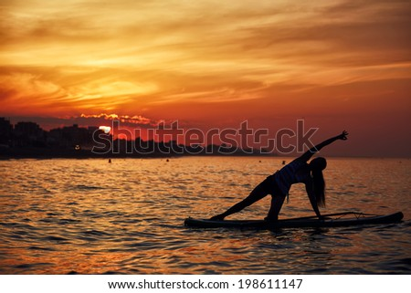 Fine and perfect silhouette of a girl engage paddle surf yoga at the amazing sunset over the sea, harmony with the nature in yoga meditation - stock photo