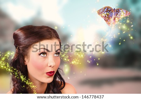 Fine art beauty and fashion portrait of a fairy tale girl with amazing makeup watching magic butterflies spiral light in a colorful spring garden. Fantasy design - stock photo