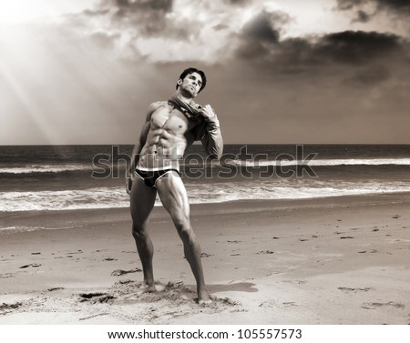 Fine art body portrait of a beautiful muscular man on the beach with dramatic sky and sepia toning - stock photo