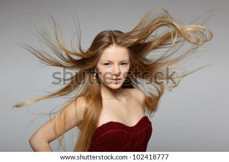 Fine art fashion portrait of blond fashion model posing with hair fluttering in the wind - stock photo