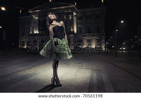 Fine art photo of a beautiful woman in front of a building - stock photo