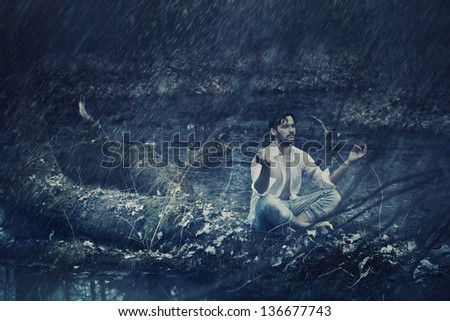 Fine art photo of a man meditating in rain - stock photo