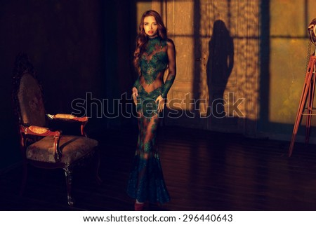 Fine art photo of young stunning elegant woman in long green luxury evening dress posing in empty room at sunset with delicate shadows - stock photo