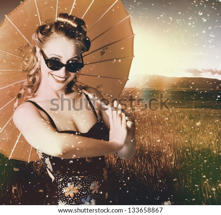 Fine art portrait of an elegant vintage American pin-up girl holding parasol in droplets of falling rain when walking in a summer field - stock photo