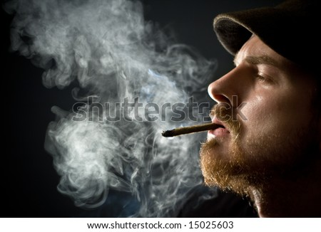 Fine art portrait of masculine guy smoking a cigar - stock photo