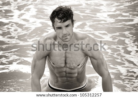 Fine art sepia toned portrait of a beautiful muscular shirtless man in the water - stock photo