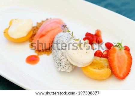 Fine dining dessert, Strawberry ice cream, poppy seed mousse and fresh fruit - stock photo
