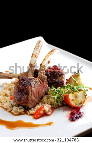 Fine dining roasted Lamb Chops on whole grain rice, mini aubergines and a sauce garnished with beerot, tomato and basil - stock photo