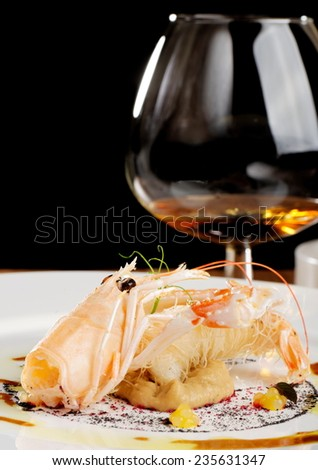 Fine dining Scampi / Norway lobster on Aubergine cream with tapioca with a glass of a Cognac - stock photo