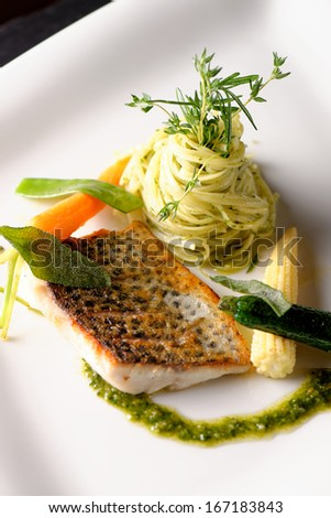 Fine dining, Trout fish fillet breaded in herbs and spice with basil pasta - stock photo