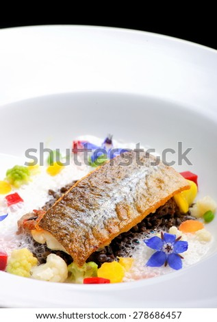 Fine dining, white fish fillet breaded in herbs and spice with shrimps and vegetables - stock photo