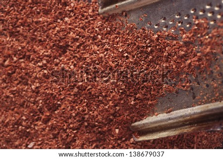 fine grated chocolate on grater , shallow dof - stock photo