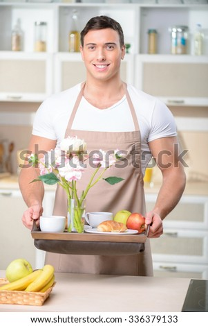 Fine-looking brunch. Smiling strongly built man holds a tray of exquisite breakfast serving. - stock photo