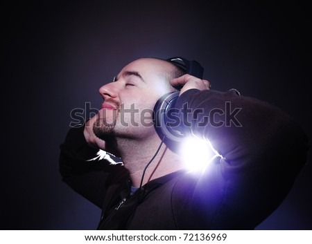 fine portrait of man listening music with headphone - stock photo